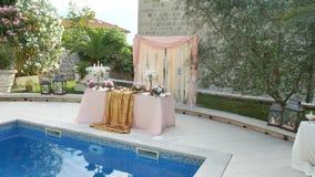 Una tabla en el banquete de la boda cerca de la piscina Decoración de la boda metrajes