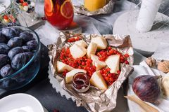 Una tabla hermosa con los bocados, mentiras del queso con las pasas rojas fotografía de archivo