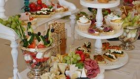 Una tabla larga con muchas placas con la comida en banquete del día de fiesta fotografía de archivo