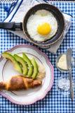 Una tabla puso con el huevo frito, aguacate, cruasán Imágenes de archivo libres de regalías