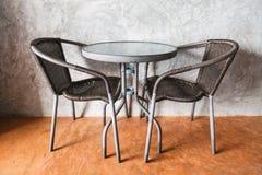 Una tabla y sillas en el piso concreto marrón Foto de archivo libre de regalías