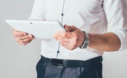 Una tableta blanca está en las manos de un hombre Él se coloca en una camisa blanca y pantalones negros y lee la información del  fotografía de archivo