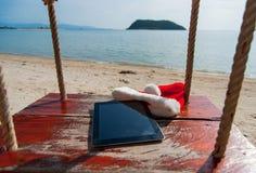 Una tableta con un sombrero de la Navidad foto de archivo