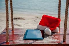 Una tableta con un sombrero de la Navidad fotografía de archivo
