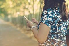 Una tableta del uso de la mujer para el negocio durante viaje imagen de archivo libre de regalías