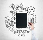 Una tableta, dispositivo digital es rodeada por los iconos exhaustos del negocio Una mano está dibujando una carta de barra Foto de archivo