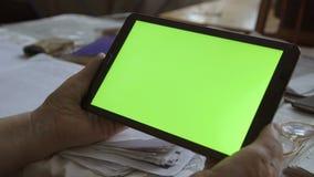 Una tableta en blanco en la orientación del paisaje con las manos de un screenin del verde 4K almacen de metraje de vídeo
