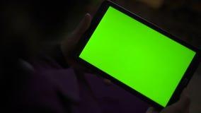 Una tableta en blanco en la orientación del paisaje con las manos de un screenin del verde lentamente metrajes