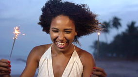 Una tarde de la celebración con una mujer hermosa que sostiene la bengala en la playa en la cámara lenta metrajes