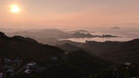 Una tarde hermosa que miraba el sol fijó detrás de las montañas de Taiwán, creando un contexto de oro contra los cielos claros Foto de archivo libre de regalías