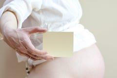 Una tarjeta con un hueco en la mano de embarazada Foto de archivo