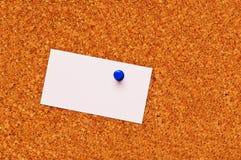Una tarjeta de visita en blanco en una tarjeta del corcho Foto de archivo