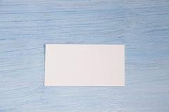 Una tarjeta de visita miente en el centro en un fondo azul imagen de archivo libre de regalías
