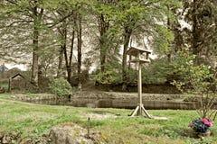 Una tavola dell'uccello davanti al grande stagno del giardino circondato dal ` s dell'albero e dal ` s dell'arbusto con un cielo  immagini stock