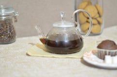 Una tavola di prima colazione dell'insieme Bollitore di vetro rotondo, due tazze, muffin, zucchero, una latta di caffè Fotografie Stock Libere da Diritti