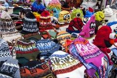 Una tavola in pieno dei beanies colourful da vendere al mercato indiano di Otavolo nell'Ecuador fotografia stock