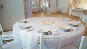 Una tavola rotonda nella priorità alta è una tavola rotonda coperta di tovaglia e servita con i piatti ed i vetri Chiavari video d archivio
