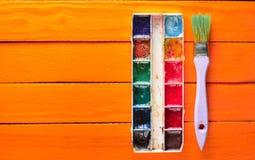Una tavolozza della pittura dell'acquerello e una spazzola per la verniciatura sui bordi di legno arancio Vista superiore Copi lo Fotografie Stock Libere da Diritti