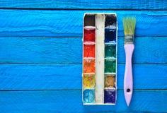 Una tavolozza della pittura dell'acquerello e una spazzola per la verniciatura sull'dei bordi di legno blu Vista superiore Copi l Immagine Stock Libera da Diritti