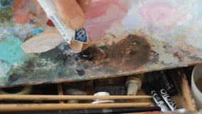 Una tavolozza variopinta della pittura ad olio su un bordo del compensato La mano schiaccia la pittura acrilica da un tubo video d archivio