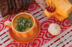 Una taza anaranjada de sopa de la calabaza, varias rebanadas de pan de centeno, pedazos de calabaza fresca y ajo Foto de archivo libre de regalías