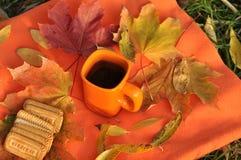Una taza anaranjada de té, de hojas de arce coloridas y de galletas en una superficie anaranjada Foto de archivo libre de regalías