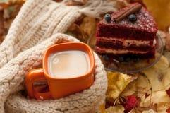 Una taza anaranjada de té de la leche, un beige hizo punto la bufanda, un pedazo de torta apetizing con los arándanos, las hojas  Imagenes de archivo