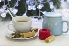Una taza blanca con el platillo, cuenco de azúcar, una madeja de hilos, árbol de navidad en la parte posterior Imagenes de archivo