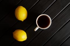 Una taza blanca con los soportes del té negro en una tabla negra al lado de dos limones amarillos minimalism Luz del d?a fotografía de archivo