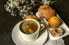 Una taza blanca de café instantáneo con la placa de galletas Foto de archivo