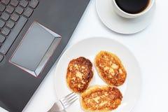 Una taza blanca de café y de una placa con la cuajada, crepes del requesón para el desayuno en la tabla cerca del ordenador portá fotos de archivo