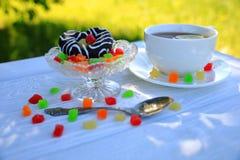 Una taza blanca de té, de galleta del chocolate y de mermelada foto de archivo