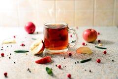 Una taza caliente de té con las manzanas y las bayas de serbal foto de archivo libre de regalías