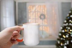 Una taza con una bebida caliente en la mano en un fondo de las decoraciones de la Navidad Fotografía de archivo