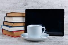 Una taza con café al lado de una tableta y una pila de diversos libros foreground foto de archivo