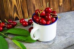 Una taza con los cherrys en la tabla de madera Foto de archivo