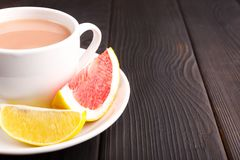 Una taza con un cacao y algunas rebanadas de limón y de pomelo dentro Fotografía de archivo libre de regalías
