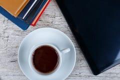 Una taza con un café al lado de una tableta y de diversos libros en un fondo de madera Visión superior Imágenes de archivo libres de regalías