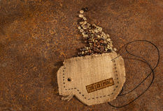 Una taza cosida en yute con la aguja y alambre por completo de los granos de café Foto de archivo libre de regalías