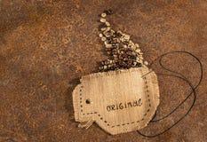 Una taza cosida en yute con la aguja y alambre por completo de los granos de café Imágenes de archivo libres de regalías