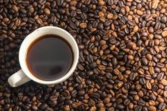 Una taza de café blanca con el fondo del grano de café Fotos de archivo