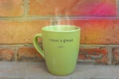 Una taza de café caliente con humo y de texto en una pared Imagenes de archivo