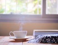 Una taza de café caliente con humo y de un libro con caliente en la tabla de madera, fondo de la ventana fotos de archivo libres de regalías