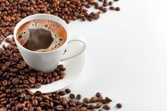 Una taza de café caliente con los granos de café en un fondo blanco Imagen de archivo