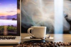 Una taza de café caliente con vapor caliente y humo asados de café granos y café express en, lugar de trabajo en una tienda del c foto de archivo libre de regalías