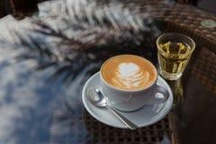 Una taza de café caliente en la tabla de cristal foto de archivo