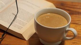 Una taza de café de cerámica blanca con crema al lado de un libro y de los vidrios de lectura, sentándose encima de una mesa de c fotografía de archivo libre de regalías