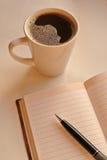 Una taza de café con el cuaderno y la pluma negra en salida del sol se encienden fotos de archivo