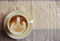 Una taza de café con el modelo de la hoja Foto de archivo libre de regalías