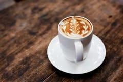 Una taza de café con el modelo de la hoja Imagenes de archivo